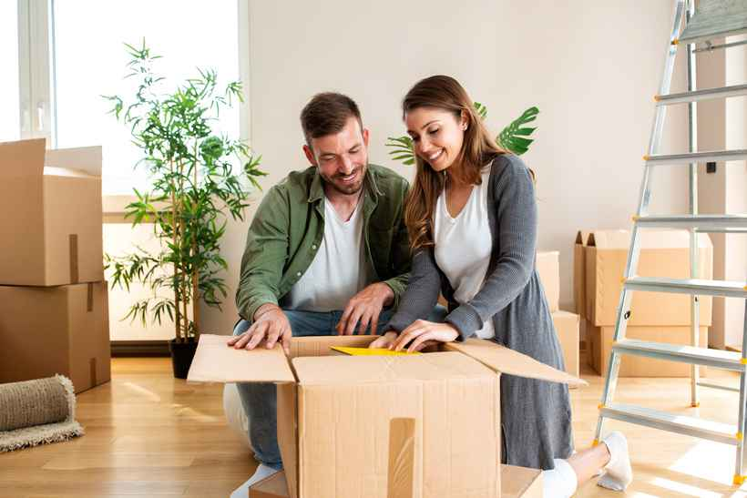 Happy couple unpacking boxes in their new apartment and smiling