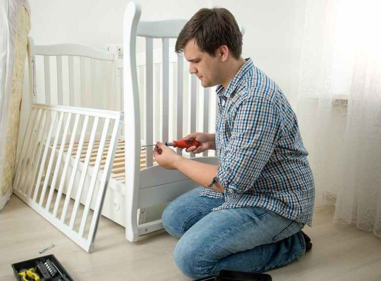 Young man assembling baby's cot