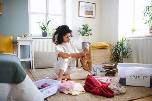 Young woman sorting wardrobe indoors at home, charity donation concept.
